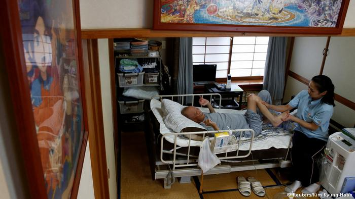 A massage therapist and Mitsuru Niinuma in his bedroom (Reuters/Kim Kyung-Hoon)