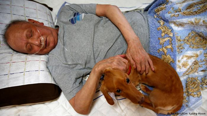 Mitsuru Niinuma lying in bed with his dog Rin (Reuters/Kim Kyung-Hoon)