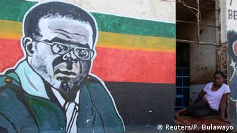 A woman sits in a doorway looking at a Mugabe mural