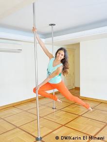 Manar el Mokadam hängt lächelnd an einer Pole-Dance-Stange (Foto: DW/Karin El Minawi)