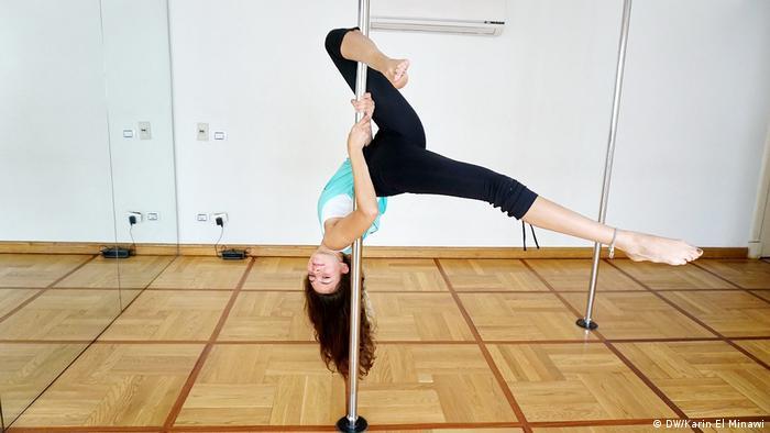 Rihan Soliman hängt kopfüber an einer Pole-Dance-Stange (Foto: DW/Karin El Minawi)