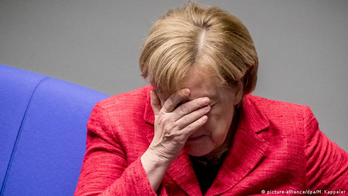 German Chancellor Angela Merkel covers her eyes (picture-alliance/dpa/M. Kappeler)