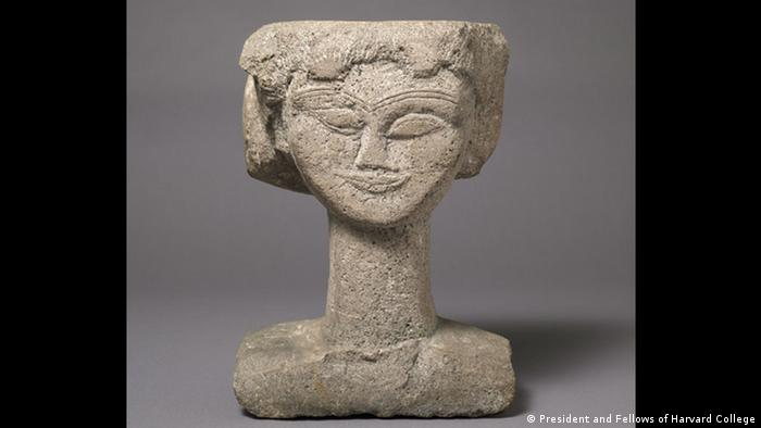 A statue of a female head made by Modigliani shows a geometric smiling face (President and Fellows of Harvard College)