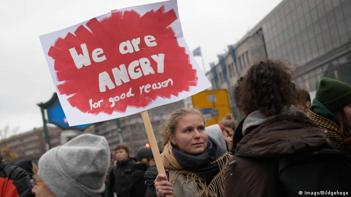 A woman in a demonstration holds up a sign reading We are angry