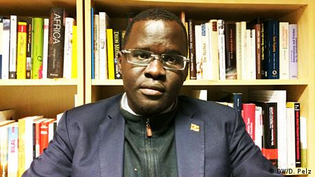 Nicholas Opiyo, Ugandan human rights activist, sitting in front of a bookshelf, wearing a navy blue blazer.
