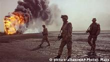 FILE -- In this March 7, 1991 file photo, a U.S. Marine patrol walks across the charred oil landscape near a burning well during perimeter security patrol near Kuwait City. Twenty five years after the first U.S. Marines swept across the border into Kuwait in the 1991 Gulf War, American forces find themselves battling the extremist Islamic State group, born out of al-Qaida, in the splintered territories of Iraq and Syria. The Arab allies that joined the 1991 coalition are fighting their own conflicts both at home and abroad, as Iran vies for greater regional power following a nuclear deal with world powers. (AP Photo/John Gaps III, File) |