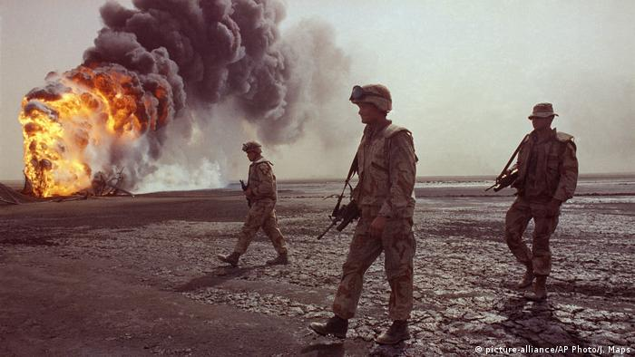 US troops walk across the charred oil landscape near a burning well during perimeter security patrol near Kuwait City