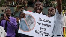 Man holds a placard reading, 'Mugabe go home and REST!!!!!'
