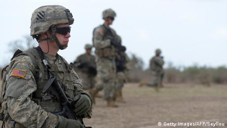 An American solider in full combat gear during training in Senegal stands to the side of the frame and looks ahead. Approximately four other soldiers are in the background.