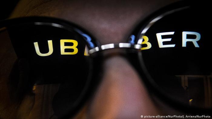 Eine Person mit einer Sonnenbrille, in der sich der Schriftzug Uber spiegelt (Foto: Picture Alliance)