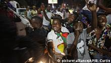 Zimbabweans drink, dance, and sing as they celebrate at night at an intersection in downtown Harare, Zimbabwe (picture-alliance/AP/B. Curtis)