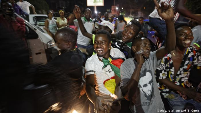Zimbabweans drink, dance, and sing as they celebrate at night at an intersection in downtown Harare, Zimbabwe