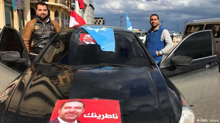 Mossab Cherraf and a friend stand at their car with a poster of Hariri on the hood