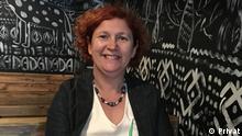 ***ACHTUNG: Nur im Zusammenhang mit dem Deutschlehrerporträt verwenden!*** Deutschlehrerin Svetlana aus Serbien sitzt auf einer Holzbank an einem Holztisch. Vor ihr steht ein Getränk mit einem Strohhalm. Rechte: Privat