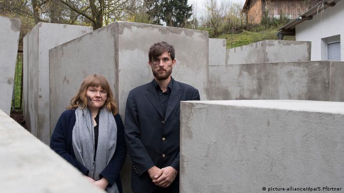 Jenni Moli und Morius Enden (von links) vom Zentrum für Politische Schönheit stehen im Denkmal der Schande in Sichtweite des AfD-Politikers Höcke