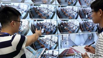 Chinese invigilators check a big screen showing live footages from surveillance cameras in classrooms