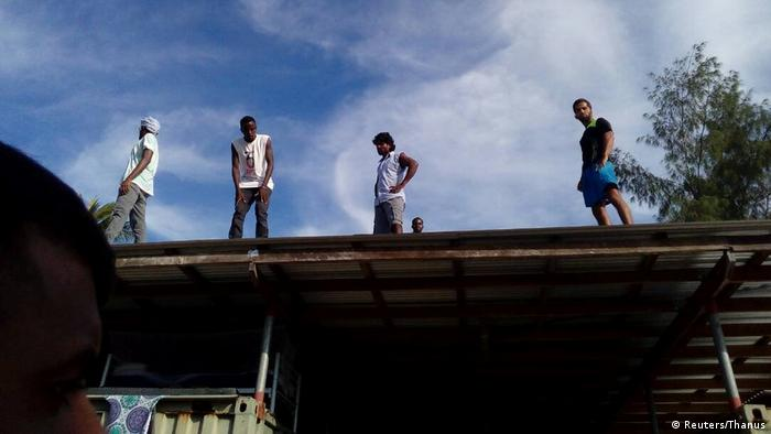 Four asylum seekers climb on top of a building in order to avoid police in the Manus Island detention center in Papua New Guinea (Reuters/Thanus)