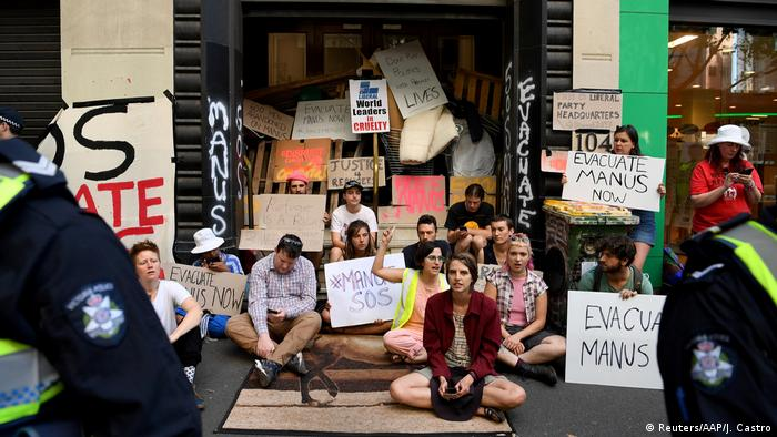 Protesters block the entrance to the Victorian Liberal party offices in Melbourne, with signs reading #Manus SOS and Evacuate Manus Now (Reuters/AAP/J. Castro)