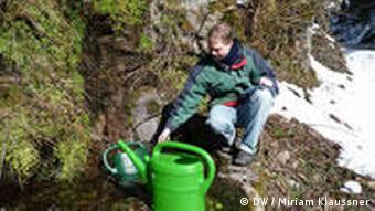Ulrich Weiner kniet mit einer Gießkanne an einer Quelle (Foto: Miriam Klaussner)