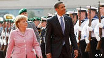 German Chancellor Angela Merkel and U.S. President Barack Obama walk along the guard of honour in Baden-Baden