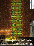 Instalación de colores y luces azules y verdes: cuelga del techo frente a una pared marrón. Jorge Pardo.