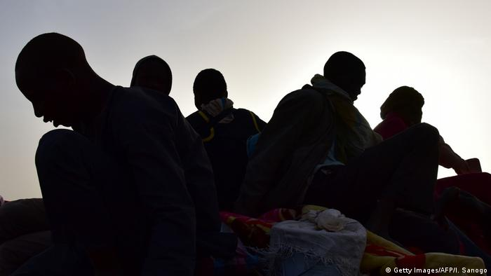 A group of people seen in silhouette, symbolising migrants