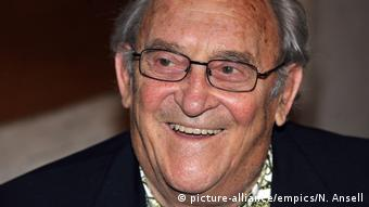 Close up photo of Denis Goldberg wearing glasses and smiling