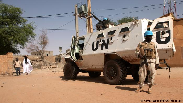 A UN blue helmet soldier stands by a white UN military vehicle in Timbuktu