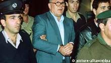 Der Angeklagte (M) wird am 26. Oktober 1987 in den Gerichtssaal geführt. Demjanjuk war 1986 von den USA nach Israel ausgeliefert worden. Ihm wurde wegen des Vorwurfs, als Wachmann Iwan der Schreckliche Verbrechen im KZ Treblinka begangen zu haben, 1988 vor einem Sondergericht der Prozeß gemacht. Am 18. April 1988 wurde er wegen Verbrechen gegen die Menschlichkeit und das jüdische Volk schuldig gesprochen und am 25. April 1988 zum Tode durch den Strang verurteilt. Der Oberste Gerichtshof in Israel hob am 29. Juli 1993 das Todesurteil wegen Zweifel an seiner Identität auf.