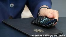 Mit ihrem Mobiltelefon und Tablet-Computer vor sich verfolgt Bundeskanzlerin Angela Merkel (CDU) am 03.07.2015 während der Bundestagssitzung im Reichstagsgebäude in Berlin die Debatte um Zusammenarbeit im Bereich des Verfassungsschutzes. Foto: Wolfgang Kumm/dpa  