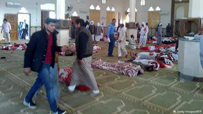 Men walk by bodies lying on the floor of the Rawda mosque after a terrorist attack