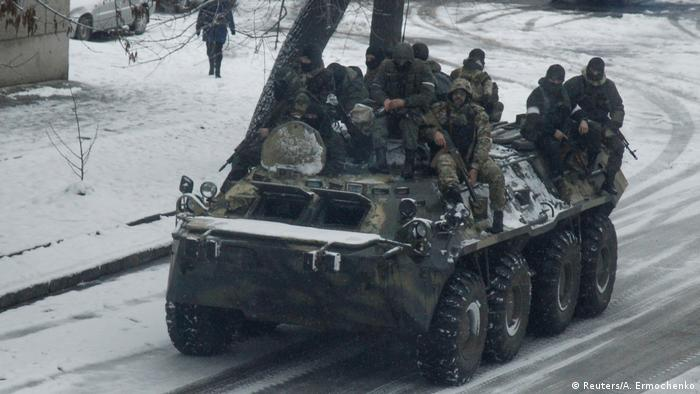 Armed men sit atop armoured personnel carrier (APC) as they drive in the centre of rebel-controlled city of Luhansk