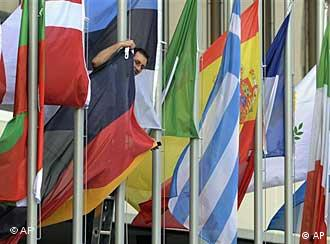 A man adjusts the German flag between the flags of the EU member states in front of the Congress Center in Prague, Czech Republic