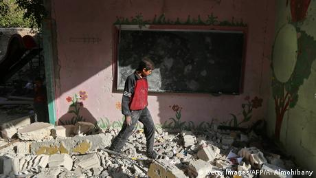 Boy walking on rubble in the town of Hamouria, near Damascus (Getty Images/AFP/A. Almohibany)