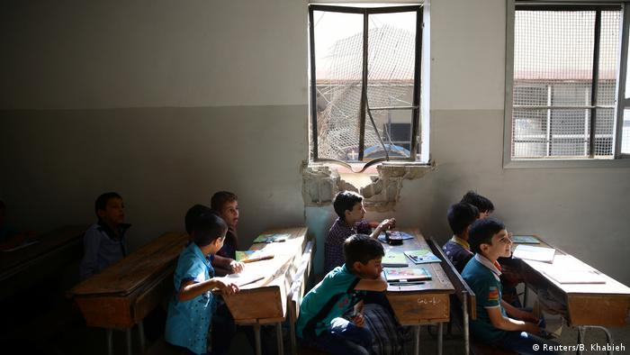 Kids in classroom with damaged window in Douma, Syria (Reuters/B. Khabieh)