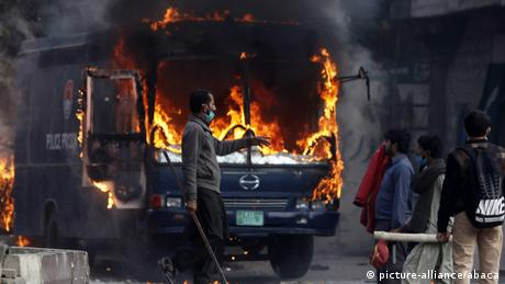 Pakistani protesters are seen beside a burning police van which was set on fire by them after security forces launched a crackdown.