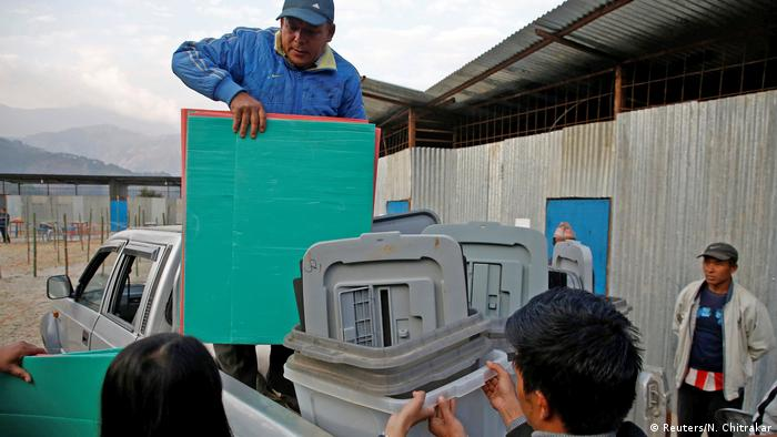 Men unload election materials from a truck ahead of the vote in Nepal