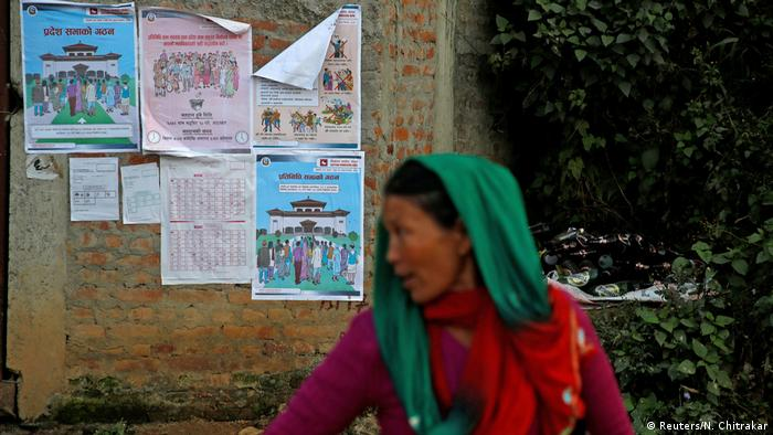A woman walks in front off Nepal campaign posters on a building wall (Reuters/N. Chitrakar)