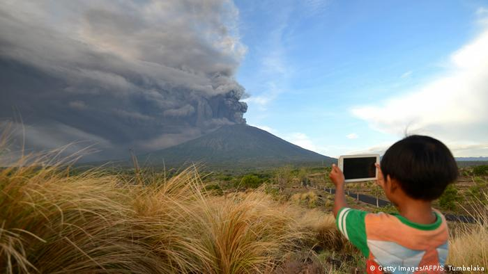 A boy takes a photo of the volcano with a smart phone
