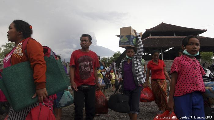 People carry belongings as they evacuate
