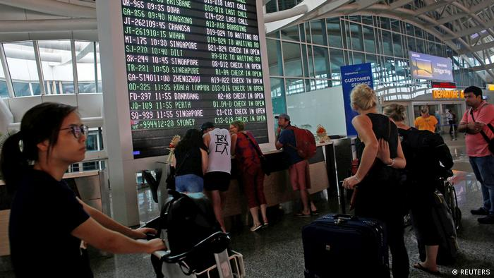 Passengers look at flight schedules at Bali's international airport