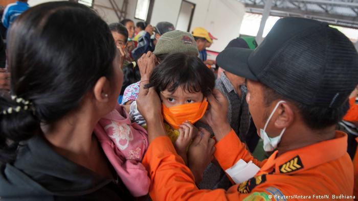 Солдат надевает на ребенка маску для защиты от пепла