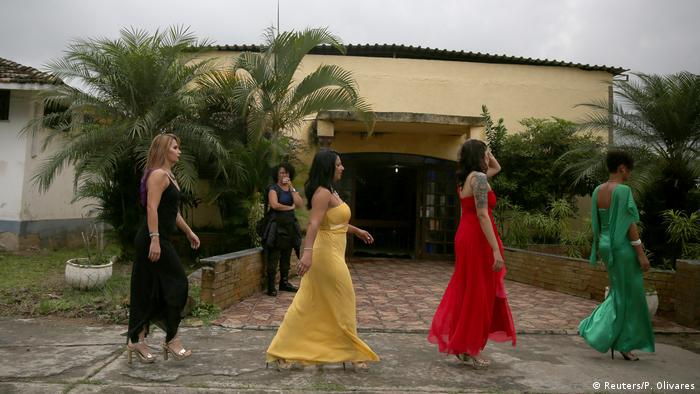 The women, in colorful dresses, walk down a path, with palm trees in the background.