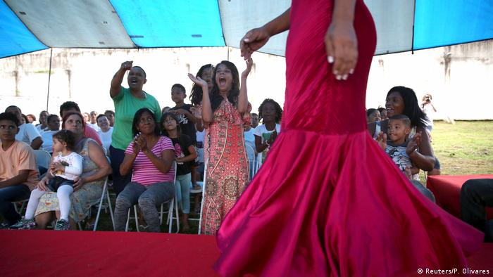 The women walk out in front of an audience, who look like family members, with small children sitting on people's laps.