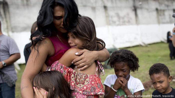 A contestant hugs two of her children. They are all crying.