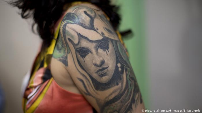 A close-up photo of the winner's tattooed shoulder.