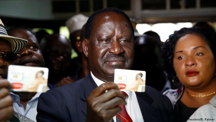 Raila Odinga holds up small plastic card (Reuters/B. Ratner)