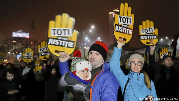People hold signs that read All for Justice during a protest outside the government headquarters in Bucharest, Romania