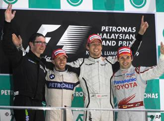 Winner Brawn GP Formula One driver Jenson Button of Britain, second right, third placed Toyota driver Timo Glock of Germany, right, runner up BMW Sauber driver Nick Heidfeld of Germany, second left, and a Brawn GP race engineer, left, celebrate on the podium after the Malaysian Formula One Grand Prix at the Sepang racetrack in Kuala Lumpur, Malaysia, Sunday, April 5, 2009. The race was terminated due to heavy rain after only 32 of 56 laps were taken.