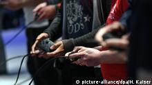 22.08.2017****Besucher halten am 22.08.2017 am Pressetag der Computerspielemesse Gamescom 2017 in Koeln (Nordrhein-Westfalen) Controller fuer Spielkonsolen in den Haenden. Foto: Henning Kaiser | Verwendung weltweit
